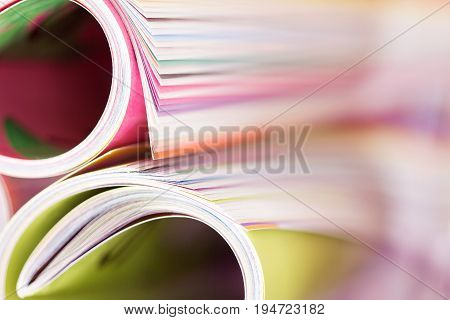 Close up edge of colorful magazine stacking roll with blurry bookshelf background for bublication and publishing concept extremely DOF