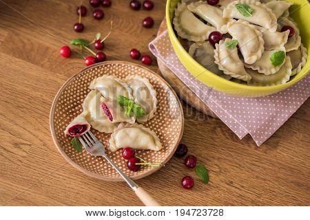 Dumplings with cherries on wooden background.