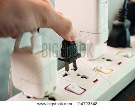 Hand holding electric plug Multiple socket with connected plugs.