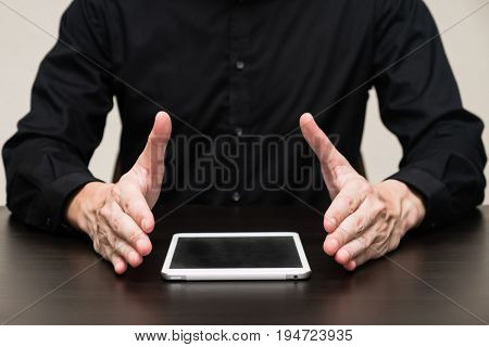 Businessman showing modern tablet on the table.