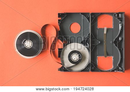 Opened video cassette tape on orange background.