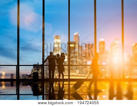 Family travelers dragging suitcases walked to travel abroad in the bus terminal would leave the country over blurred other travelers waiting plane and city at night interior with large windows.