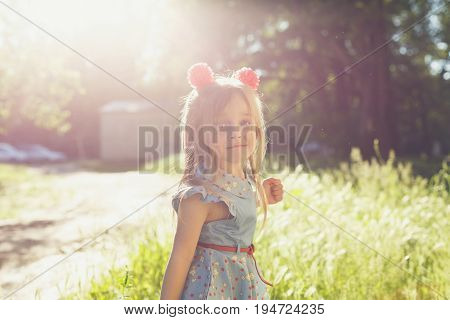 Little cute girl with hairpins in a city park. She makes faces. Backlight of the setting sun.