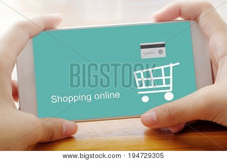 Hand holding smart phone with shopping online screen background business E-commerce technology and digital marketing