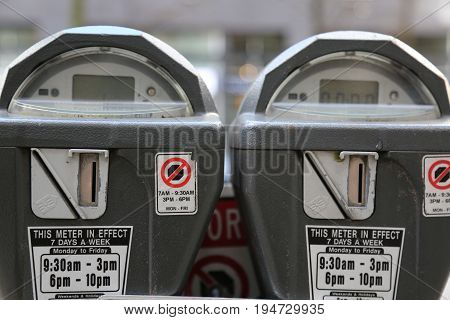 Two parking meters accepting coins closeup no people