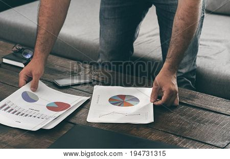 Man analyzes the sales report on the sofa at home. Analysis of sales and revenue concept