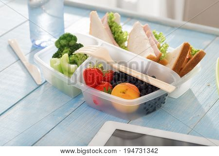 Full lunch box of healthy food. Sandwich strawberry peach blueberries broccoli and celery in a lunch box on wooden table. Helpful Lunch concept