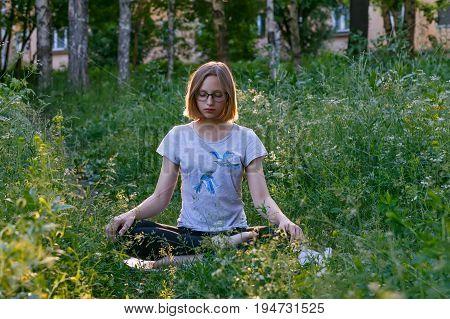 Teenage girl meditating in lotus position in citypark