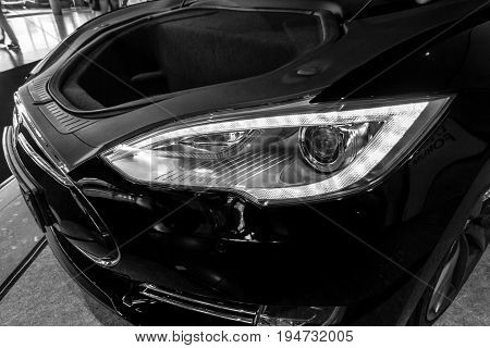 STUTTGART GERMANY - MARCH 17 2016: Headlamp and trunk of full-size luxury car Tesla Model S AWD 90D 2015. Black and white. Europe's greatest classic car exhibition