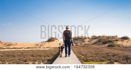 Man with dog walking on the wooden path on the beach and looking into the distance of the ocean.