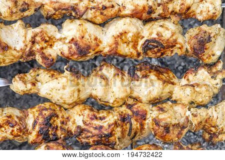 Shish kebab close-up. Slices of meat in marinade preparing on fire