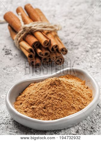 Close up view of ground cinnamon in trendy plate and cinnamon sticks on gray cement background. Vertical.