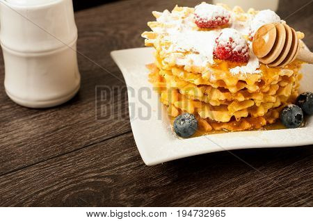 Belgian waffles with raspberries and sieving sugar powder and honey served with jug of milk on a white table.