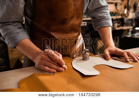 Close up of a male shoemaker cutting leather textile at workshop