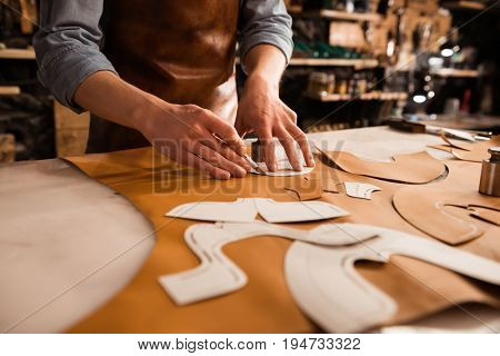 Close up of a shoemaker measuring and cutting leather in a workshop