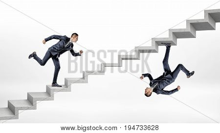 Two businessmen running up concrete stairs in overturned reflected image of each other. Career ladder. Raising up the ranks. Personal growth.