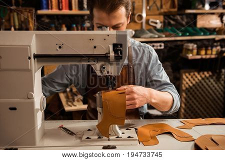 Man cobbler stitching leather patrs on a sewing machine