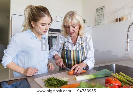 Grandmother teaching her granddaughter how to make a salad at the kitchen