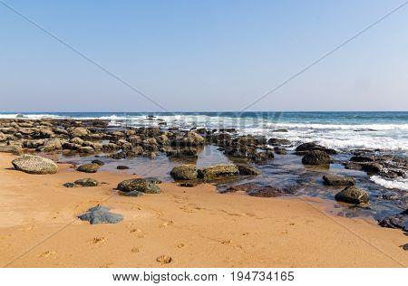 Beach Against Rocky Ocean Shoreline And Blue Sky Landscape