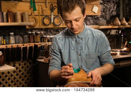 Photo of young handsome shoemaker sitting in workshop making shoes. Looking aside.