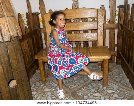 Happy look of a cute little mixed Jamaican Russian ethnicity girl. A daughter of a Russian mother and a Caribbean father sitting on a wooden bench, near a fence, imitation of the Russian Cossacks farm style, during the summer vacation in Russia