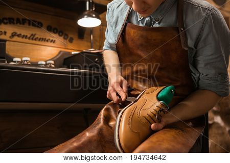 Cropped picture of young shoemaker in workshop making shoes.