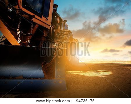 Silhouette Wheel loader Excavator with backhoe unloading sand at eathmoving works in construction site over blurred natural background sunset pastel. heavy industry and safety at work concept.