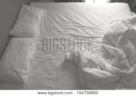Messy white bedding sheets and pillows. black and white tone