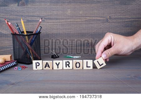 payroll concept. Wooden letters on dark background