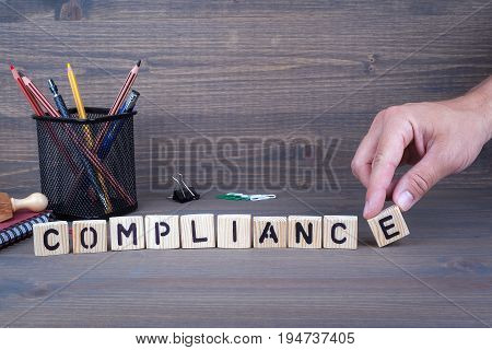 Compliance concept. Wooden letters on dark background