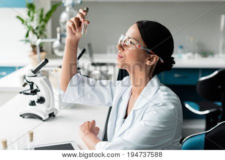 Side View Of Young Chemist In Protective Glasses And White Coat Examining Test Tube In Lab