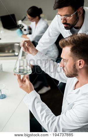 Young Male Chemists In Lab Coats Examining Reagent In Flask