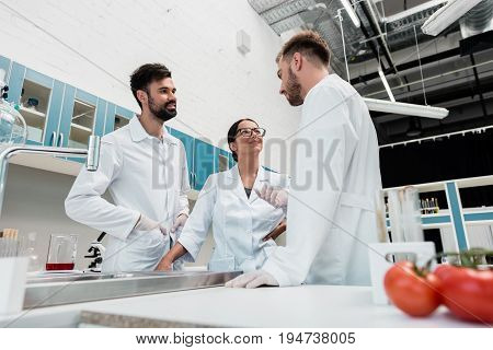 Smiling Young Chemists In White Coats Standing And Talking In Laboratory