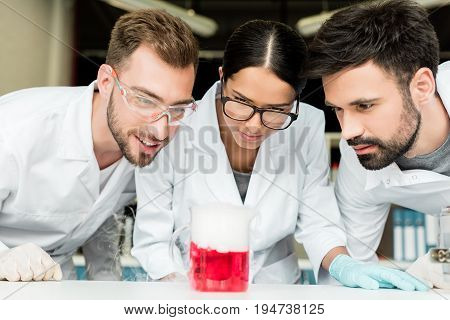 Team Of Professional Young Chemists Looking At Flask With Reagent In Laboratory
