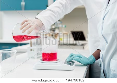 Close-up Partial View Of Scientists Making Experiment With Reagent And Flasks
