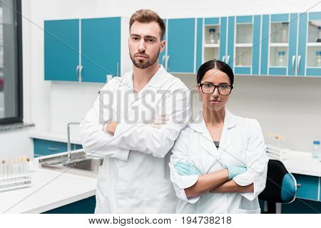 Professional Young Scientists In White Coats Standing With Crossed Arms And Looking At Camera In Lab