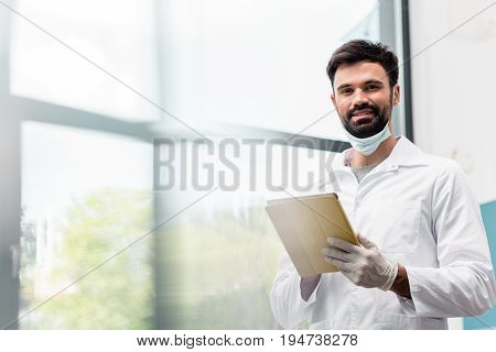 Bearded Male Scientist In Lab Coat Using Digital Tablet And Smiling At Camera