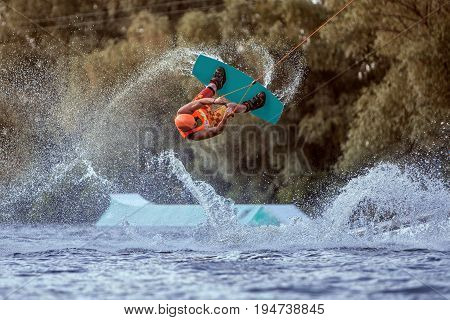 Man makes an extreme jump on wakeboarding around there are a lot of splashes and splashes of water. This is an extreme sport.