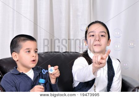 Little boy blowing soap bubbles his sister catching.