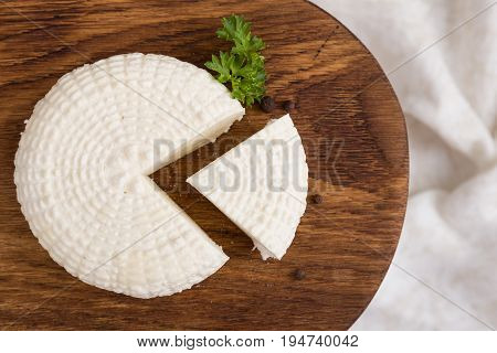 Top view on sliced round white homemade cheese - traditional milk creamy dairy product on vintage wooden board. Rustic style.