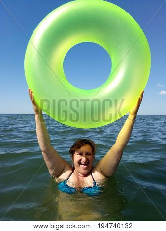 A woman holds the inflatable buoy standing in a sea laughing
