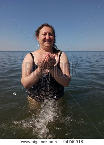 A portrait of a woman took water in her palms