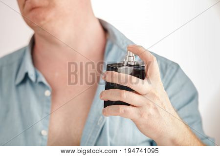 Man using perfume on self on white background