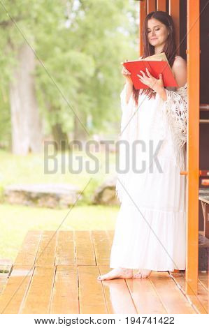 Beautiful Young Woman Reading A Book Outdoor. Standing On Terrace Or On Porch