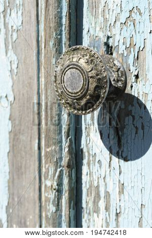 Old vintage handle on a weathered wooden door.
