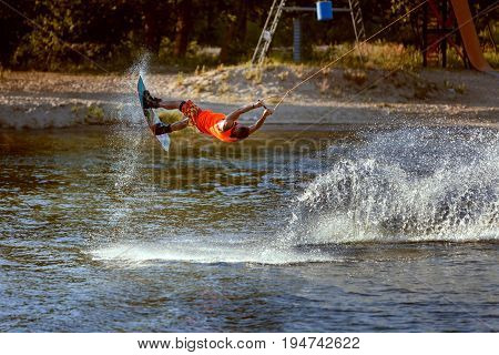 Wakeboard train in the lake is an extreme sport for men.
