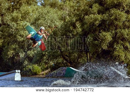 Sports training on a wakeboard. Jumping over water and tricks.