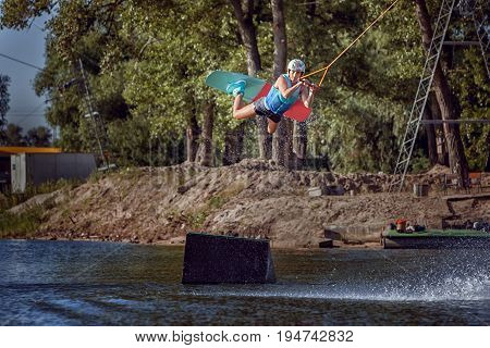 Woman extreme sports on a wakeboard to jump up.
