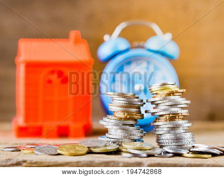 Stack of coins home model and alarm clock on wooden background. Business Finance and time of money home loan concept.