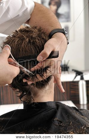 Professional hairdresser cutting childs hair in beauty saloon.